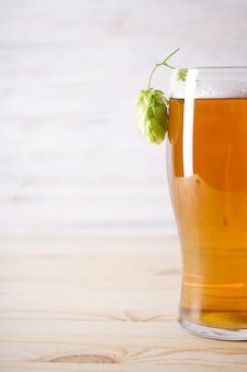 Hopfen und helles bier in glas auf holzfläche, platz für text.