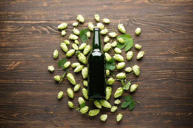Hopfen und leichtes bier in einer flasche auf einem hölzernen raum, draufsicht