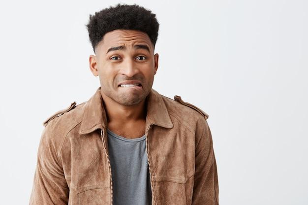 Hoppla. porträt von unglücklichen jungen gutaussehenden afroamerikanischen männern mit lockigem haar in lässigen stilvollen kleidern, die mutter mit schuldigem gesichtsausdruck betrachten, nachdem sie ihre lieblingsvase zerbrochen haben.