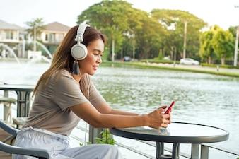 Hörende Musik des hübschen Mädchens mit den weißen Kopfhörern, die am Garten mit Sumpfhintergrund sitzen