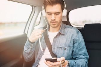 Hörende Musik des jungen Mannes auf Kopfhörer beim Reisen in das Auto