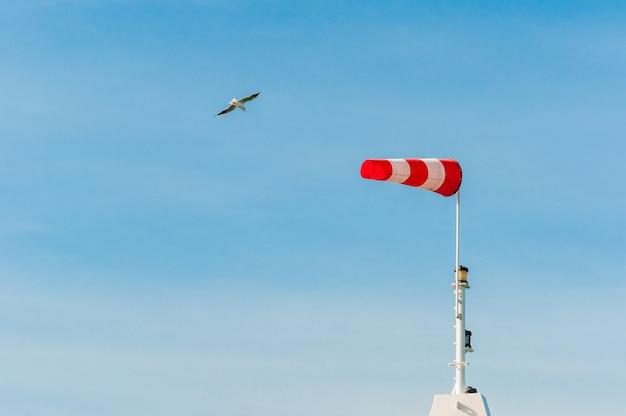 Horizontal fliegende windsackwindfahne mit blauem himmel. große vögel möwen fliegen herum.