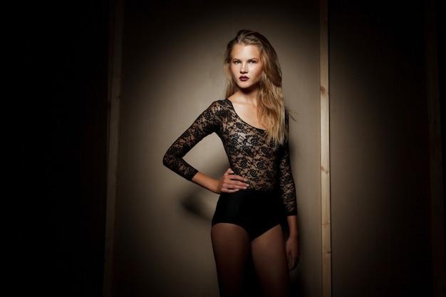 Horizontale ansicht. attraktive blonde junge frau, die in der erotischen wäsche aufwirft.
