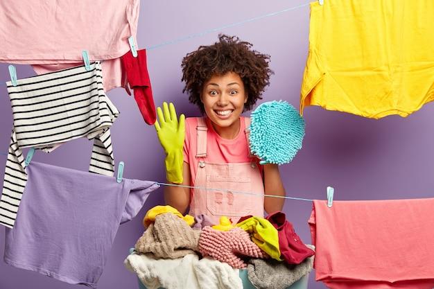 Horizontale ansicht der fröhlichen frau mit den lockigen haaren, die mit der arbeit am haus beschäftigt ist, schutzgummihandschuhe trägt, mopp zum reinigen hält, wäsche nach dem waschen hängt, glücklich fast die arbeit beendet