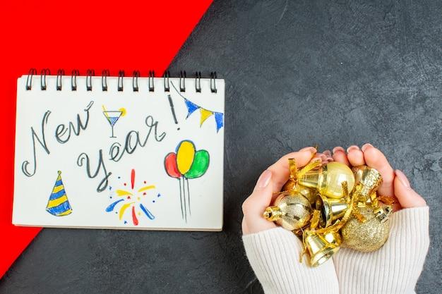 Horizontale ansicht der hand, die dekorationszubehör und notizbuch mit neujahrsschrift und zeichnungen auf dunklem hintergrund hält