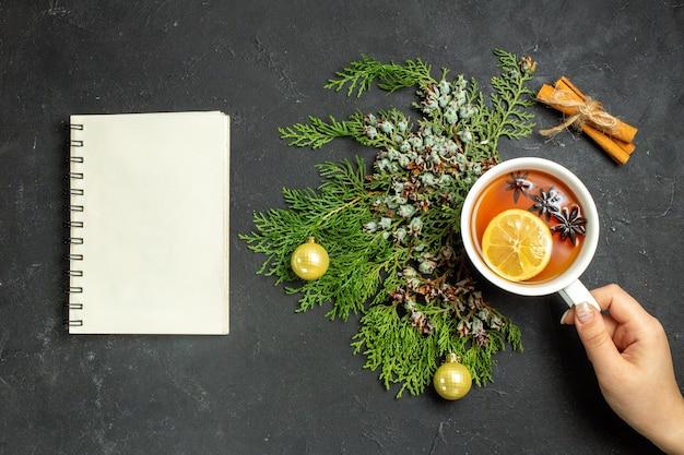 Horizontale ansicht der hand, die eine tasse schwarztee-weihnachtszubehör und zimtlimetten und ein notizbuch auf schwarzem hintergrund hält