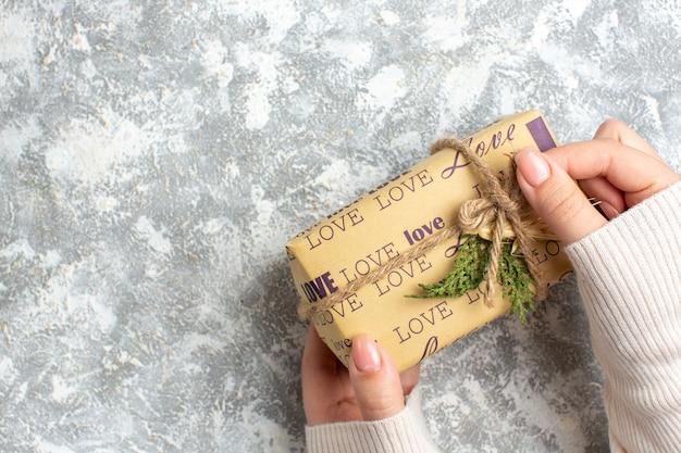 Horizontale ansicht der hand, die verpacktes geschenk für weihnachten auf der eisoberfläche hält