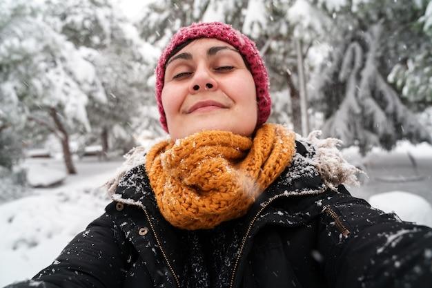Horizontale ansicht der jungen kaukasischen frau, die frische luft draußen unter dem schnee atmet.