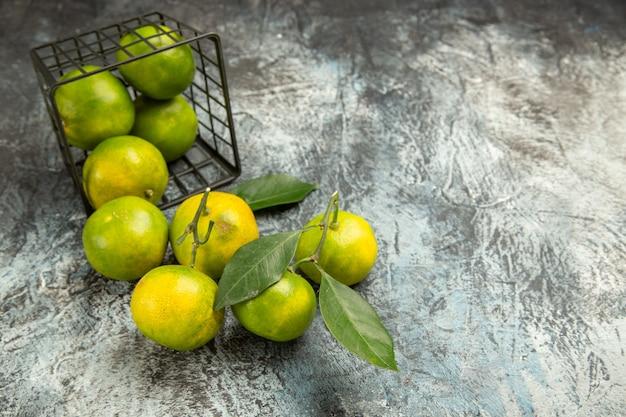 Horizontale ansicht des gefallenen korbes mit frischen grünen mandarinen in zwei hälften geschnitten und geschälte mandarinen auf grauem hintergrund