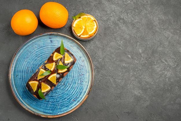 Horizontale ansicht des köstlichen kuchens und der orange auf schwarzem tisch