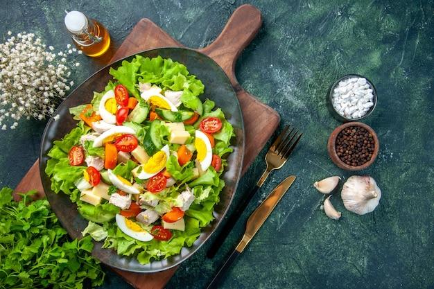 Horizontale ansicht des köstlichen salats mit vielen frischen bestandteilen auf hölzernem schneidebrettgewürzölflaschen-knoblauchbesteck gesetzt auf schwarzgrünem mischfarbenhintergrund