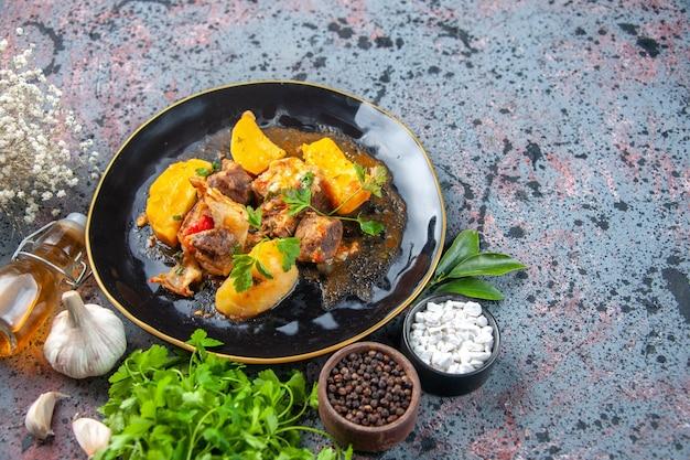 Horizontale ansicht des leckeren abendessens mit fleischkartoffeln, die mit grün in einer schwarzen platte und gewürzknoblauchölflasche serviert werden