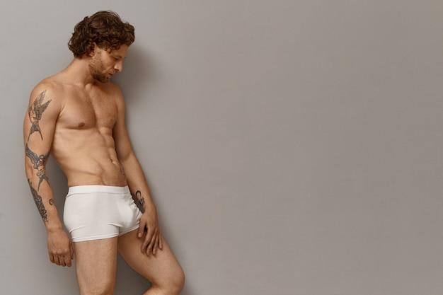 Horizontale ansicht des nackten muskulösen europäischen kerls mit bart, perfekt gebräuntem körper und tätowierten armen, die gegen leere kopyspace-wand aufwerfen, die unten mit nachdenklichem nachdenklichem gesichtsausdruck schaut