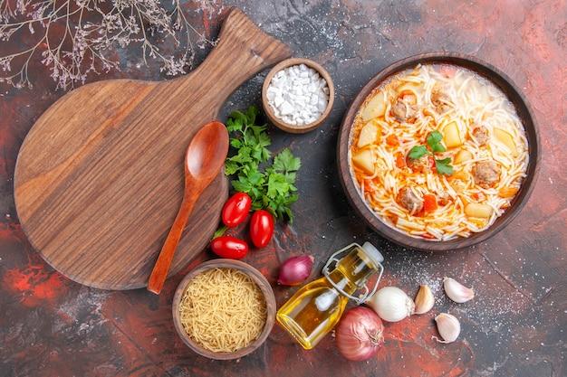 Horizontale ansicht einer köstlichen nudelsuppe mit hühnchen auf einem holzbrett, ein haufen grüner tomaten, ölflasche auf dunklem hintergrund