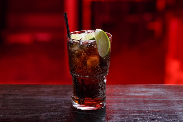Horizontale ansicht. nahaufnahme eines cuba libre-cocktails im langen glas, gin, stehend auf der bartheke, lokalisiert auf einem roten raum.