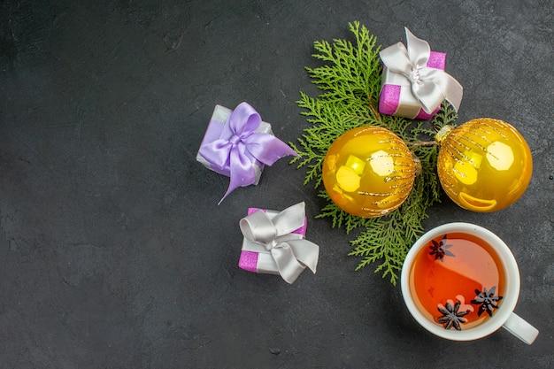 Horizontale ansicht von bunten geschenken eine tasse schwarztee-dekorationszubehör auf dunklem hintergrund