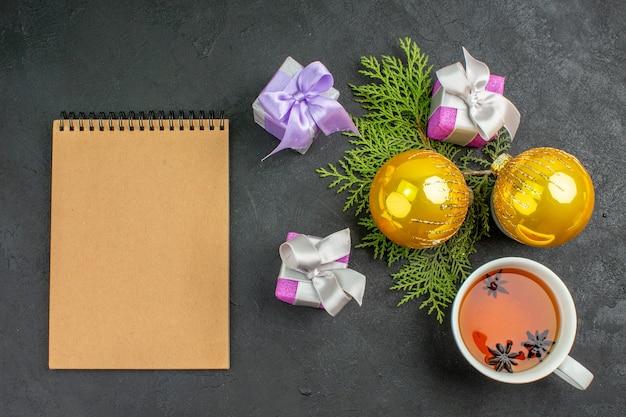 Horizontale ansicht von bunten geschenken, eine tasse schwarztee-dekorationszubehör und ein notizbuch auf dunklem hintergrund