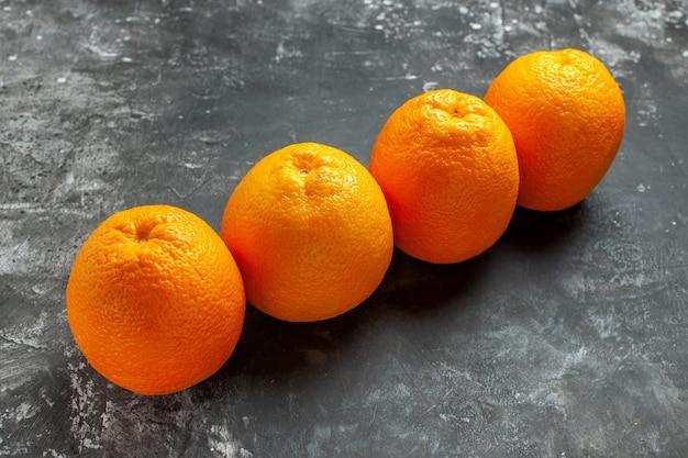 Horizontale ansicht von drei natürlichen organischen frischen orangen, die in einer reihe auf dunklem hintergrund aufgereiht sind