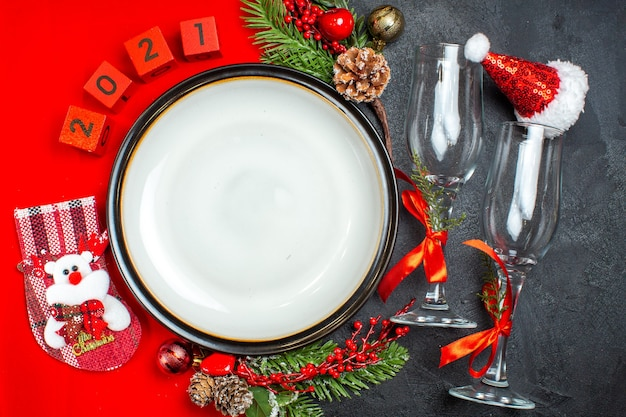 Horizontale ansicht von esstischdekorationszubehör tannenzweigen weihnachtssockenglasbecher auf dunklem tisch