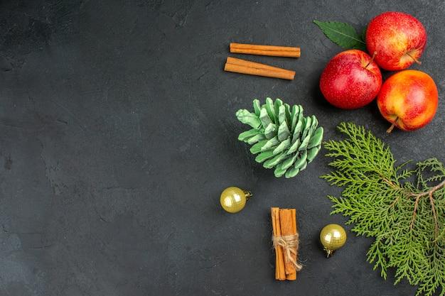 Horizontale ansicht von frischen äpfeln-zimt-limonen und dekorationszubehör auf schwarzem tisch