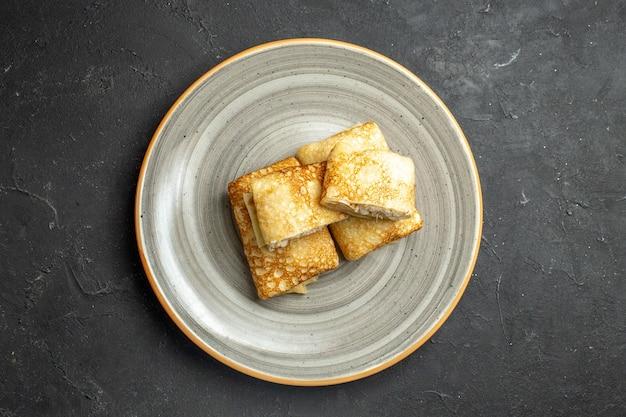 Horizontale ansicht von frischen horizontalen pfannkuchen auf einem weißen teller auf dunklem hintergrund