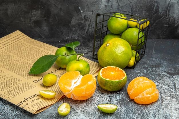 Horizontale ansicht von frischen zitrusfrüchten mit blättern, die aus einem schwarzen korb gefallen sind, der in halbe formen auf zeitung auf grauem hintergrund geschnitten ist stockfoto