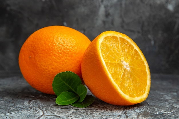 Horizontale ansicht von ganzen und halbierten frischen orangen auf grauem hintergrund
