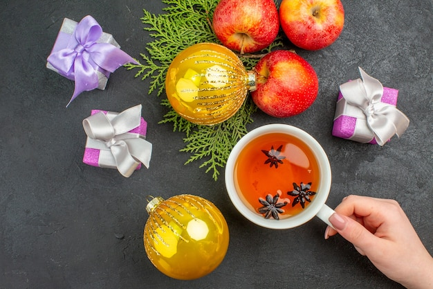 Horizontale ansicht von geschenken und dekorationszubehör für frische bio-äpfel und eine tasse schwarzen tee auf dunklem hintergrund