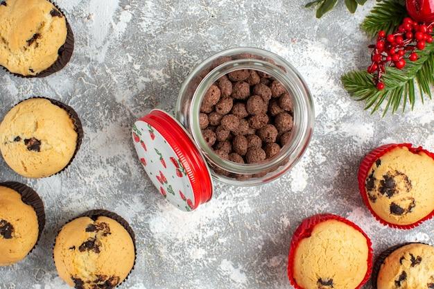 Horizontale ansicht von köstlichen kleinen cupcakes und schokolade in einem glastopf und tannenzweigen auf eisoberfläche