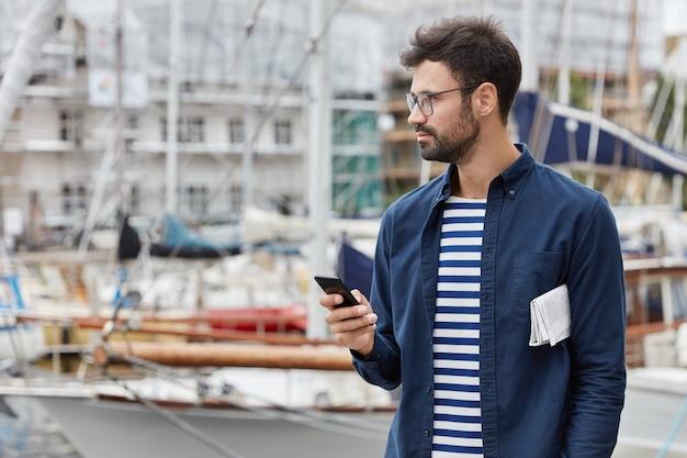 Horizontale ansicht von nachdenklichen freiberuflichen blogs in sozialen netzwerken, hält zeitgenössisches mobiltelefon