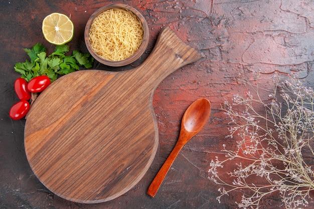 Horizontale ansicht von schneidebrett und ungekochten nudeln in einer schüssel löffel tomate zitrone und ein bündel grün auf dunklem hintergrund
