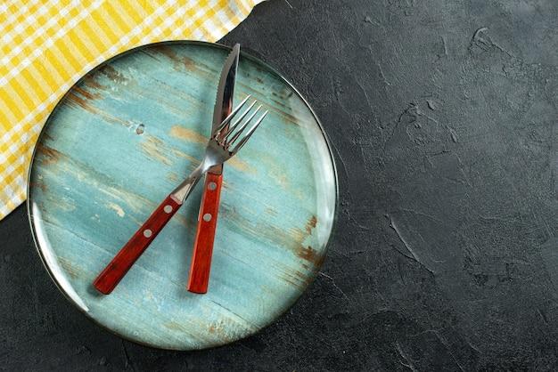 Horizontale ansicht von speisebesteck im kreuz auf blauem teller und gelbem, abgestreiftem handtuch auf der rechten seite auf dunkler oberfläche
