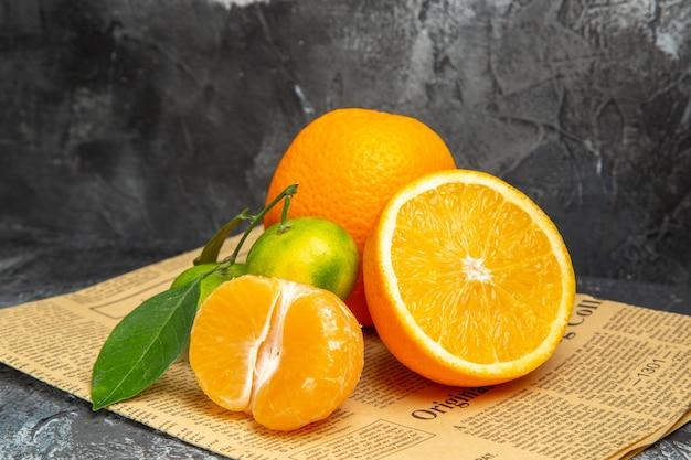 Horizontale ansicht von zitrusfrüchten in geschnittener und ganzer form mit blättern auf zeitung auf grauem hintergrund
