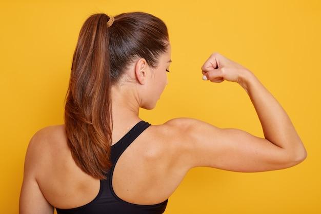 Horizontale aufnahme der attraktiven fitnessfrau, die rückwärts lokalisiert über gelbem studio aufwirft