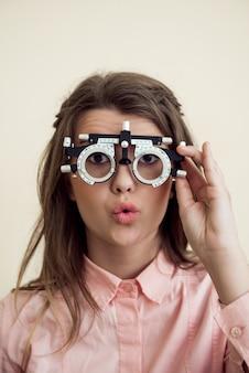 Horizontale aufnahme der aufgeregten niedlichen europäischen brünette, die vision mit phoropter prüft, daran interessiert ist, wie es funktioniert, und darauf wartet, dass optiker geeignete brille verschreibt