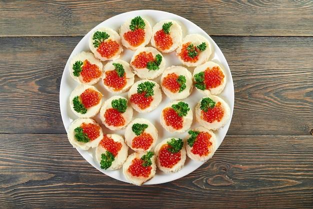 Horizontale aufnahme der draufsicht eines tellers mit gebutterten häppchen mit rotem kaviar, verziert mit luxus-teures gerichtessen des grünen copyspace, das gesundes köstliches vorspeisenrestaurant isst.