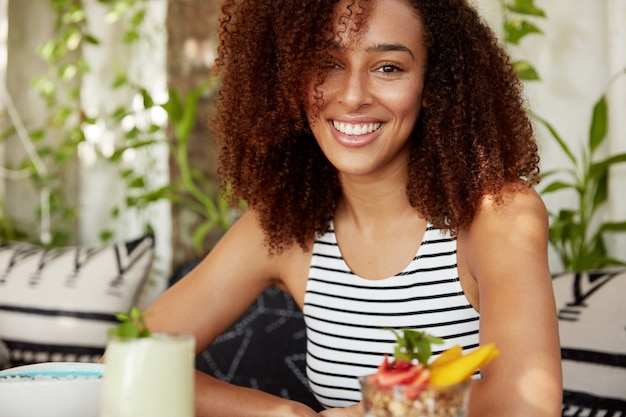 Horizontale aufnahme der dunkelhäutigen fröhlichen jungen frau mit lockigem haar, genießt freizeit am wochenende im café, isst köstlichen cocktail. afroamerikanerin froh, urlaub mit freunden zu verbringen