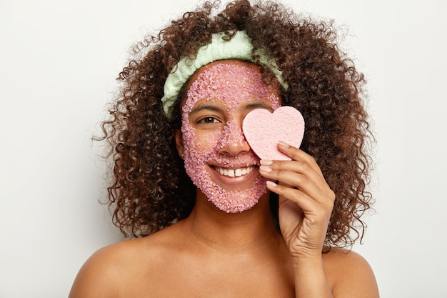 Horizontale aufnahme der entzückenden lockigen afro-frau lächelt breit, wendet abblätternde gesichtsmaske an, bedeckt auge mit herzschwamm, kümmert sich um haut, hat schönheitsroutine zu hause während des wochenendes, gesundes aussehen