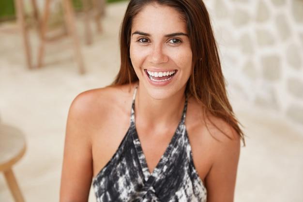 Horizontale aufnahme der entzückten attraktiven wunderschönen jungen frau mit glattem haar, trägt modische sommerkleidung, freut sich über ferien