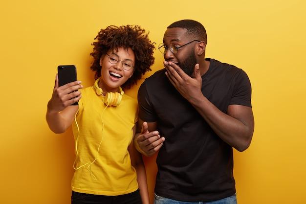 Horizontale aufnahme der fröhlichen dunkelhäutigen weiblichen und männlichen pose für selfie-porträt