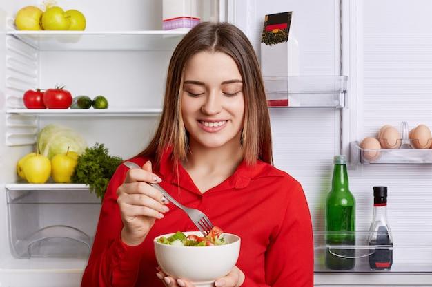 Horizontale aufnahme der fröhlichen frau hält schüssel mit frischem gemüsesalat, steht in der nähe von friedge voller produkte, hält diät. vegetarierin isst nur rohprodukte. konzept für gesunde ernährung