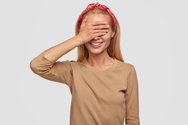 Horizontale aufnahme der fröhlichen fröhlichen schönen frau mit glücklichem ausdruck, bedeckt augen mit der hand, antizipiert überraschung