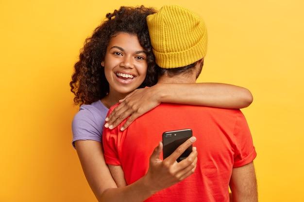 Horizontale aufnahme der glücklichen afroamerikanischen frau umarmt freund, hält handy, ist immer in kontakt, froh, freund zu treffen, drückt liebe und fürsorge aus. der gesichtslose mann tritt zurück und wird umarmt