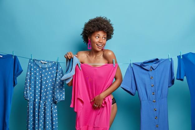 Horizontale aufnahme der glücklichen entkleideten frau versteckt sich hinter rosa kleid am seil hängen, posiert in der nähe von verschiedenen kleidungsstücken, hält schuhe in der blauen farbe, kleider für das vorstellungsgespräch, will fantastisch aussehen