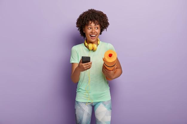 Horizontale aufnahme der glücklichen lockigen fitnessfrau hört musik über kopfhörer und smartphone während des trainings, trägt aufgerolltes karemat, gekleidet in t-shirt und leggings. menschen, die das konzept ausüben