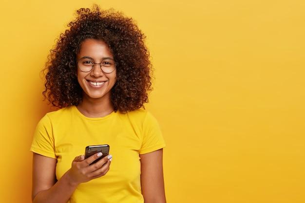 Horizontale aufnahme der hübschen frau mit angenehmem lächeln im gesicht, genießt online-kommunikation auf dem handy, liest benachrichtigung, trägt runde brille und gelbes t-shirt. technologie- und personenkonzept