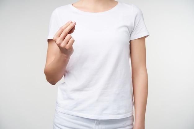 Horizontale aufnahme der jungen frau im weißen t-shirt, die ihre hand anhebt, während gedanken ohne wörter ausdrückt, wortmaler zeigend, während über weißem hintergrund aufwirft