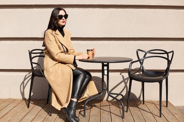 Horizontale aufnahme der jungen frau mit tasse trinkt kakao an der stadtstraßencaféterrasse, sitzt am tisch und träumt, dame trägt beigen mantel
