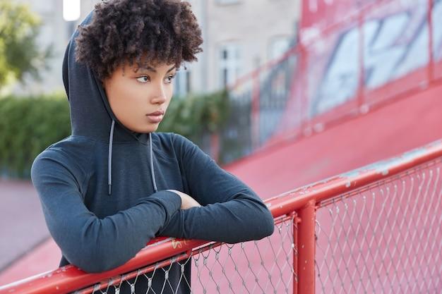 Horizontale aufnahme der nachdenklichen dunkelhäutigen frau mit afro-haarschnitt, sweatshirt