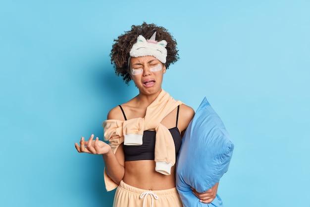 Horizontale aufnahme der niedergeschlagenen afroamerikanischen frau weint vor verzweiflung in nachtwäsche gekleidet hält kissen leidet an schlaflosigkeit wendet kollagenflecken an, die über der blauen wand isoliert sind